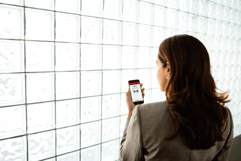 Woman in an office using the LiftMaster MyQ app