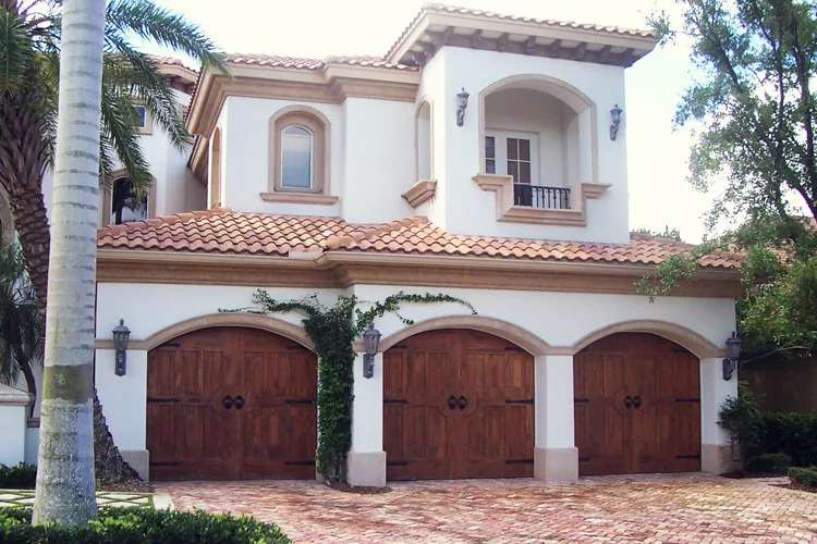 Florida home with three wooden signature series garage doors