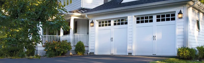 House with two white steel carriage house style garage doors